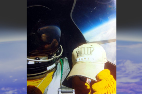 Image of g503 hat in cockpit of U2 with pilot in space suit with the curvature of the earth visible in the background.